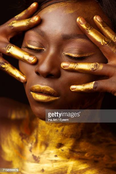 Close-Up Of Woman In Golden Face Paint