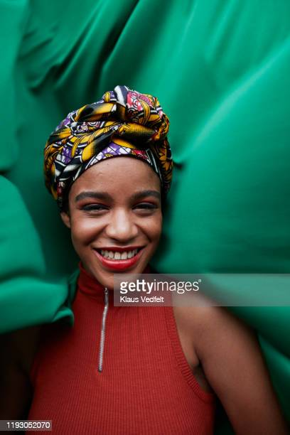 close-up of woman in headwear against green textile - headwear stock pictures, royalty-free photos & images
