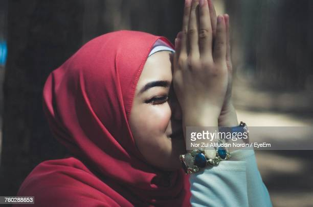 close-up of woman in hijab with hands clasped - muslim praying stock pictures, royalty-free photos & images
