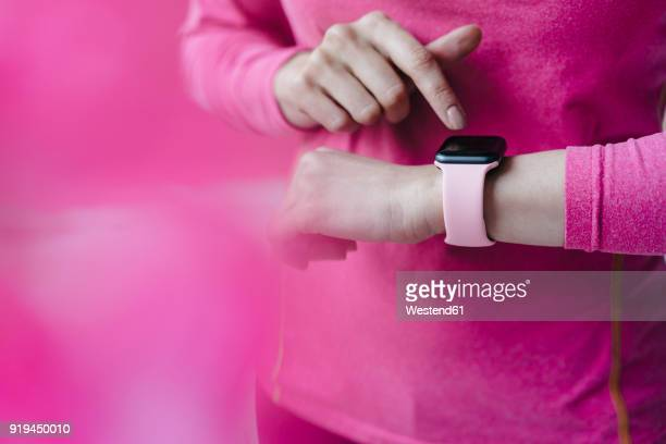 close-up of woman in pink sportswear adjusting her smartwatch - smart watch stock pictures, royalty-free photos & images