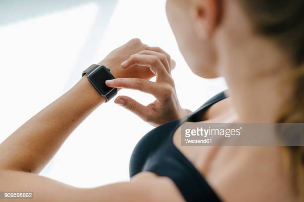 close-up of woman in sportswear adjusting her smartwatch - checking sports stock pictures, royalty-free photos & images