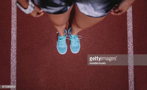 Close-up of woman in sportswear and trainers standing on running track