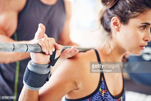 Close-up of woman lifting barbell while coach assisting her