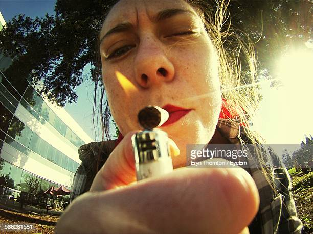 Close-Up Of Woman Lighting Cigarette Outdoors
