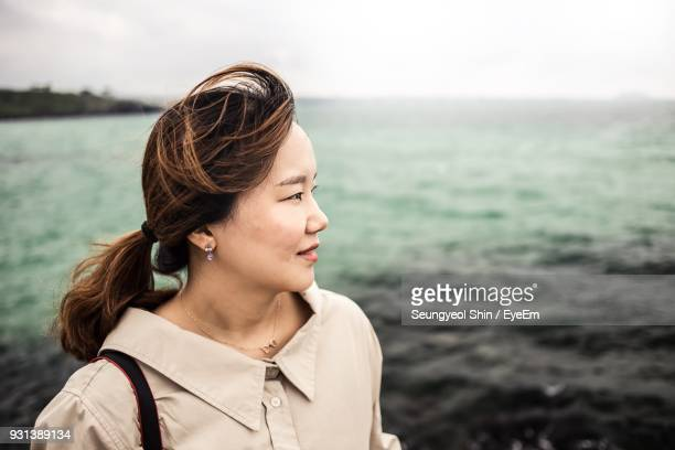 Close-Up Of Woman Looking Away Against Sea