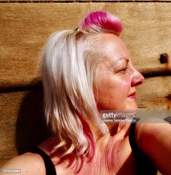 Close-Up Of Woman Looking Away Against Wall During Sunny Day
