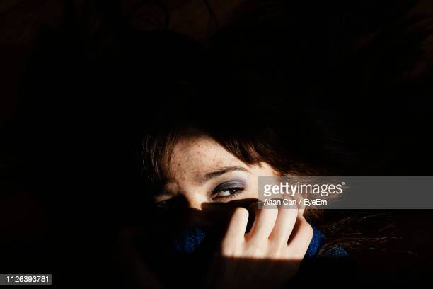 close-up of woman looking away in darkroom - obscured face stock pictures, royalty-free photos & images
