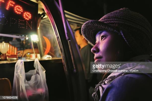 Close-Up Of Woman Looking Away In Illuminated Market