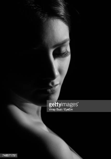 close-up of woman looking away over black background - clair obscur photos et images de collection
