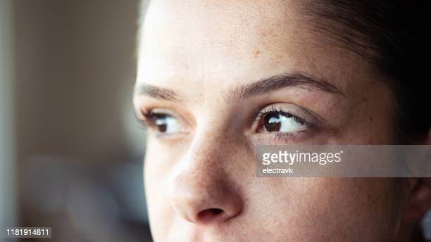 closeup of woman looking away - close up stock pictures, royalty-free photos & images