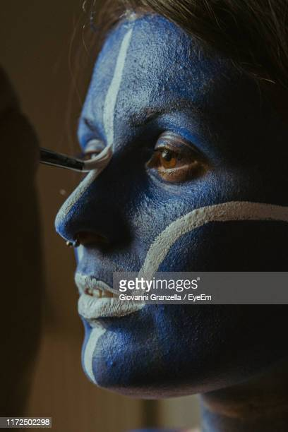 close-up of woman looking away while applying paint on face - body paint stock pictures, royalty-free photos & images