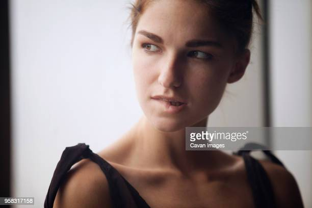 close-up of woman looking away while biting lip - biting lip stock pictures, royalty-free photos & images