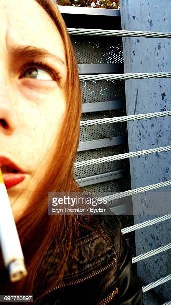 Close-Up Of Woman Looking Away While Smoking Cigarette Against Window