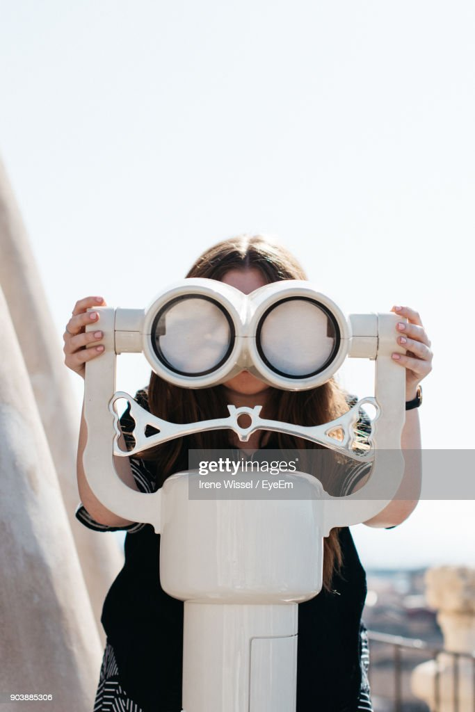 Close-Up Of Woman Looking Through Binoculars Against Clear Sky : Photo