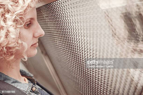 close-up of woman looking through glass window - bortes stock photos and pictures
