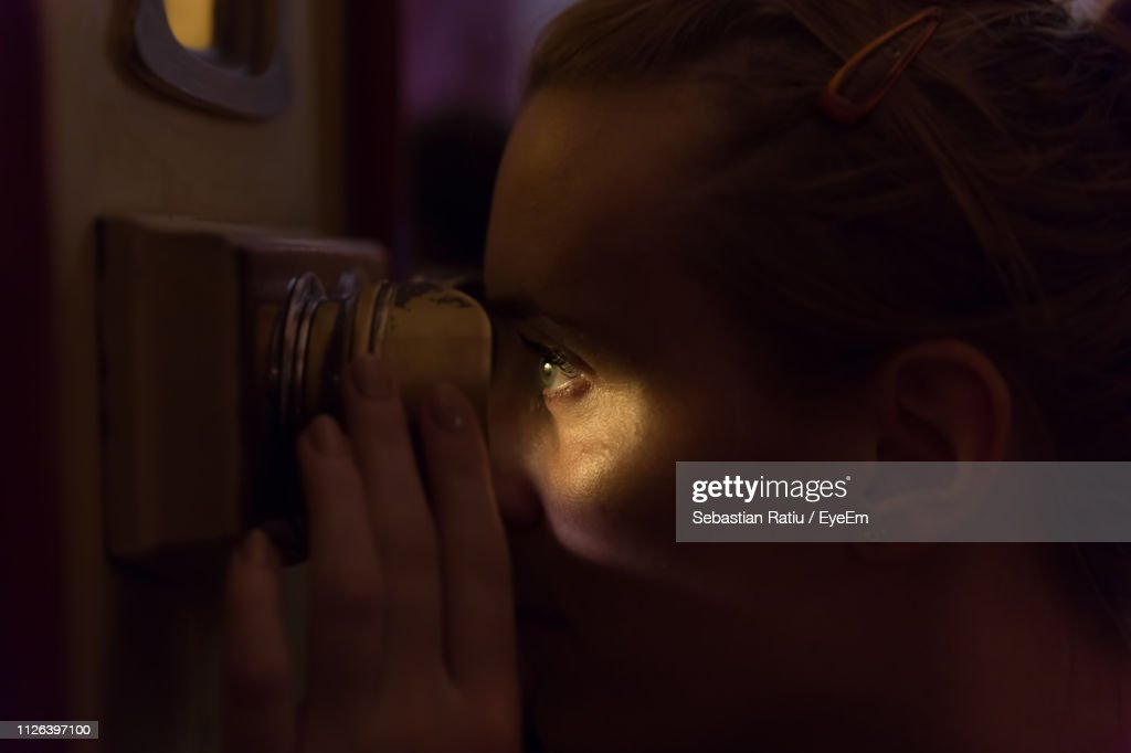 Close-Up Of Woman Looking Through Peephole In Darkroom : Stock Photo