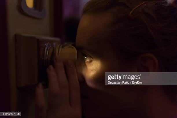 Close-Up Of Woman Looking Through Peephole In Darkroom
