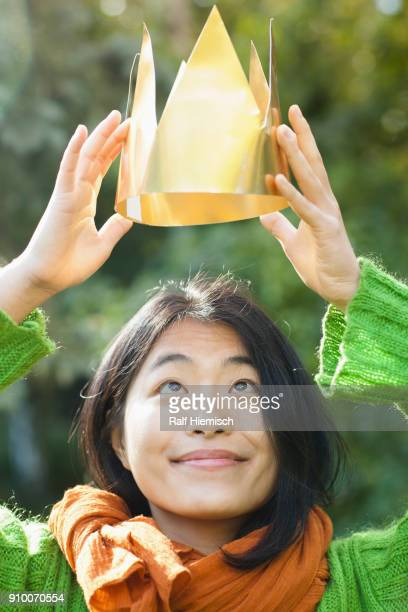 close-up of woman looking up while holding crown during sunny day - crown close up stock pictures, royalty-free photos & images