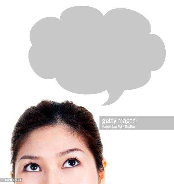 Close-Up Of Woman Looking Up With Speech Bubble Against White Background
