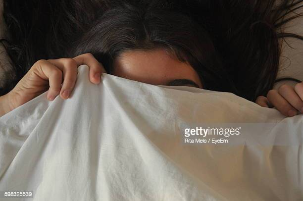Close-Up Of Woman Lying On Bed And Covering Face With Fabric