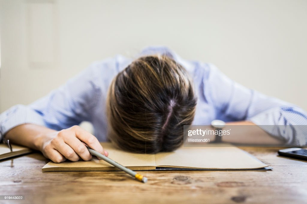 Close-up of woman lying on notebook at desk : Stock Photo