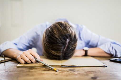 Close-up of woman lying on notebook at desk - gettyimageskorea