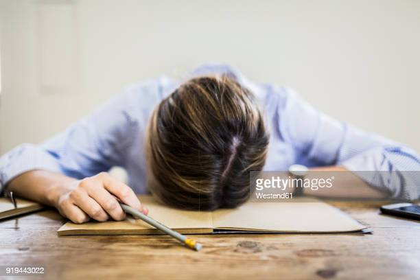 close-up of woman lying on notebook at desk - overworked stock pictures, royalty-free photos & images