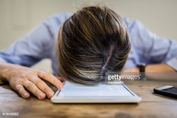 close-up of woman lying on tablet at desk - burnout stock photos and pictures