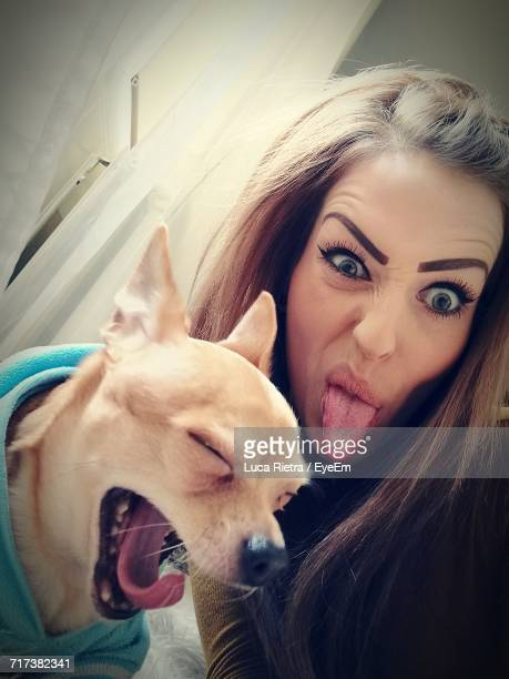 Close-Up Of Woman Making Face By Chihuahua Yawning At Home