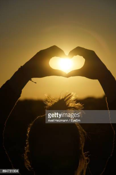 Close-Up Of Woman Making Heart Shape Against Sky During Sunset