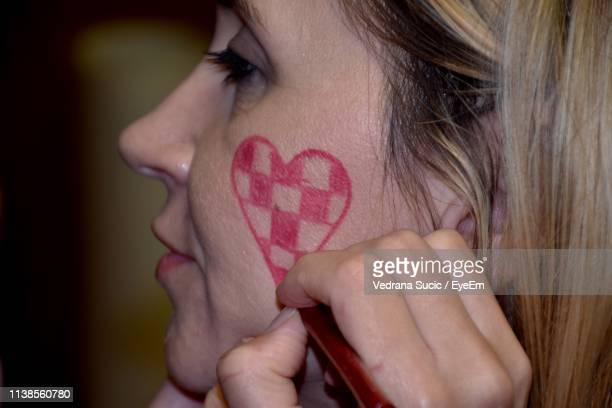close-up of woman making heart shape on cheek - cheek stock pictures, royalty-free photos & images