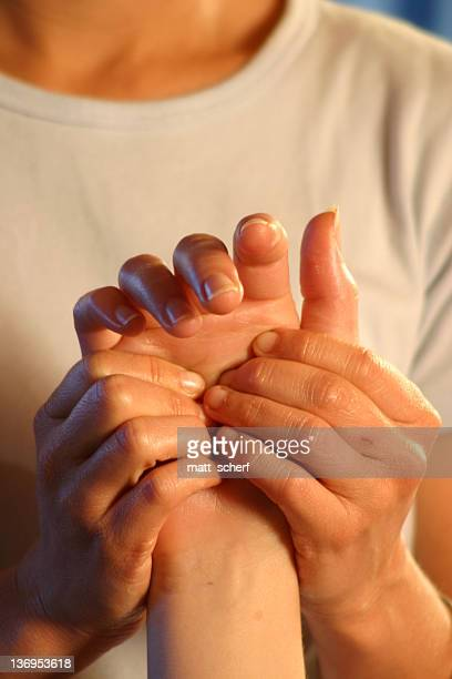 Closeup of woman masseuse massaging man's hand
