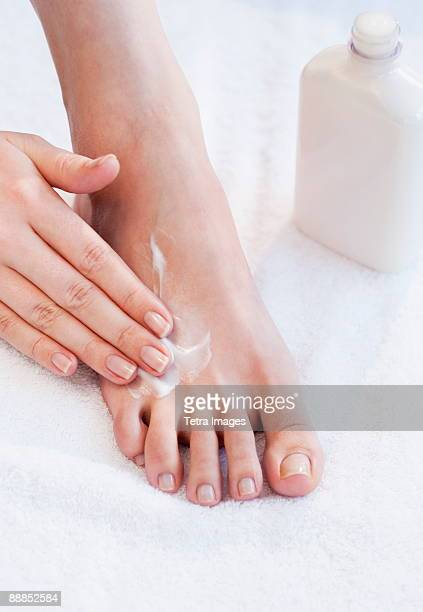 close-up of woman moisturizing foot - womens pretty feet stock pictures, royalty-free photos & images