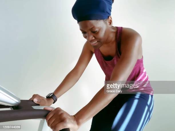 close-up of woman on exercise bike - real body fotografías e imágenes de stock
