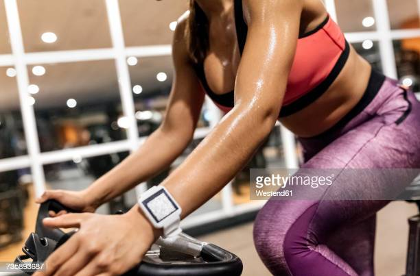 Close-up of woman on spinning bike in the gym