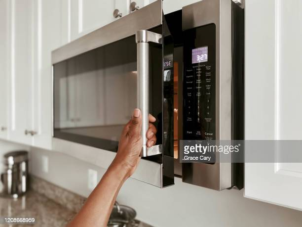 close-up of woman opening microwave - appliance stock pictures, royalty-free photos & images