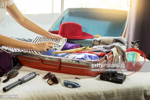 close-up of woman packing luggage on bed - pack fotografías e imágenes de stock