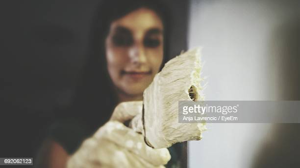 Close-Up Of Woman Painting Wall With Paint Brush