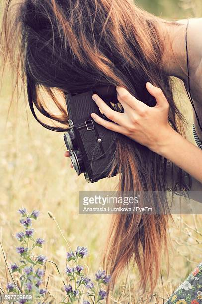 Close-Up Of Woman Photographing Flowers On Field