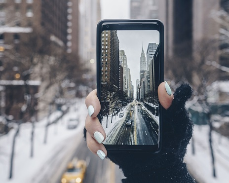 Close-Up Of Woman Photographing Through Smart Phone In Winter - gettyimageskorea