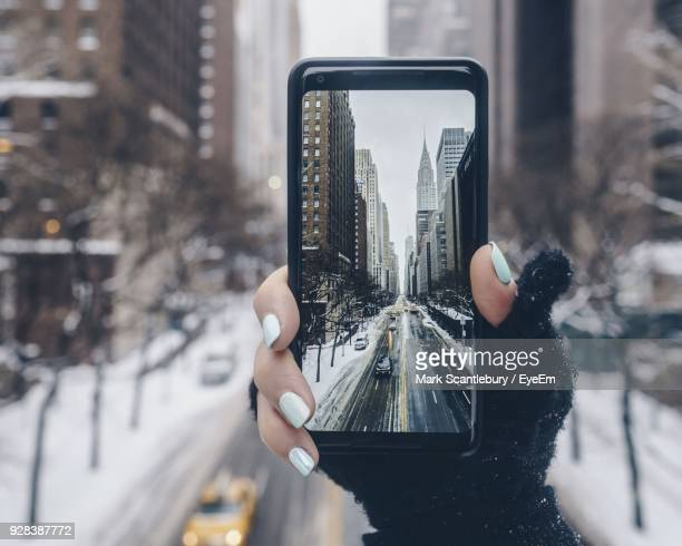 close-up of woman photographing through smart phone in winter - 手袋 ストックフォトと画像