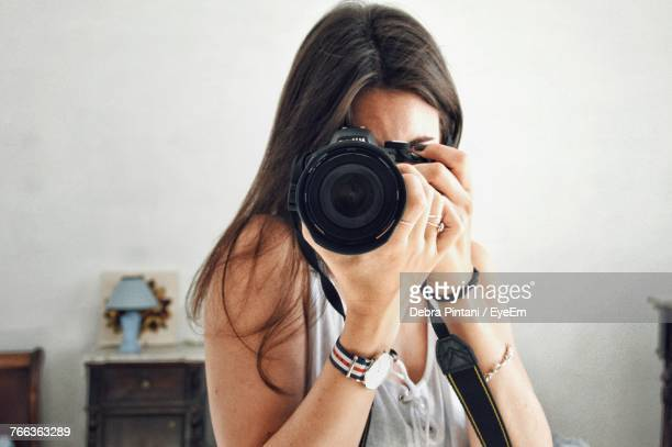 Close-Up Of Woman Photographing With Camera At Home