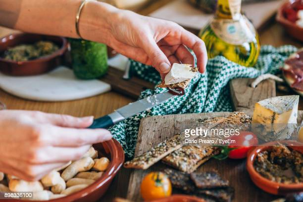 close-up of woman preparing food at table - tapas stock photos and pictures