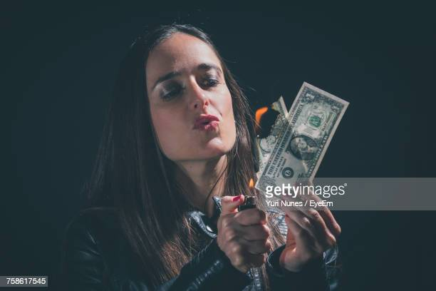 Close-Up Of Woman Puckering Lips While Burning Dollar Note Against Black Background