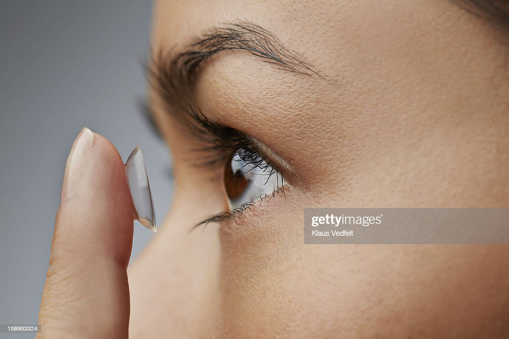 Close-up of woman putting in contact lens : Stock Photo
