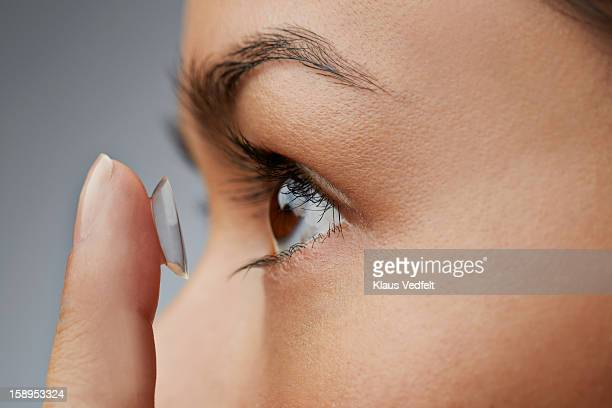 close-up of woman putting in contact lens - contacts stock photos and pictures
