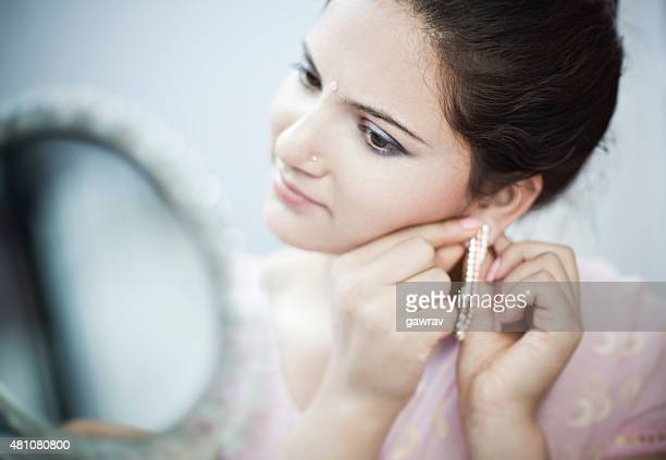 close-up of woman putting on earring and looking at mirror. - inserting stock pictures, royalty-free photos & images
