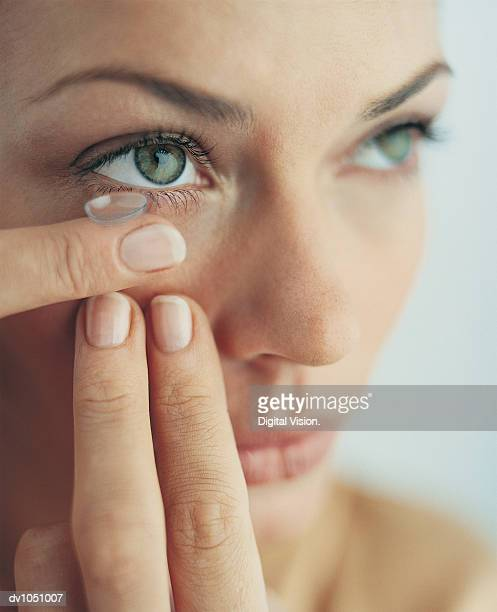 close-up of woman putting on her contact lens - contacts stock photos and pictures