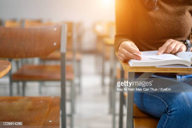 close-up of woman reading on table - college admission stock pictures, royalty-free photos & images