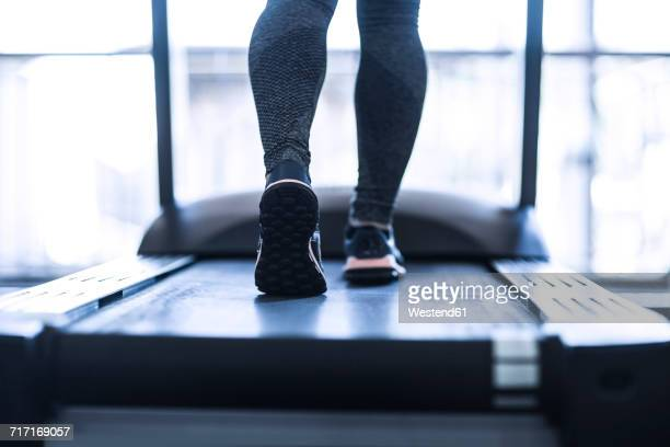 Close-up of woman running on treadmill at the gym